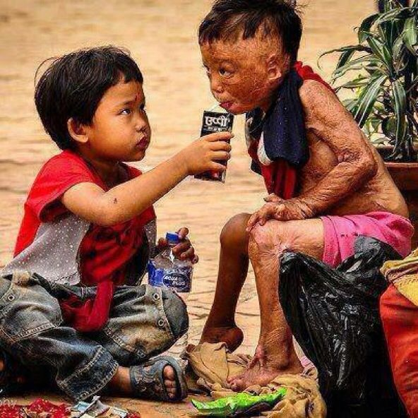 Young Child Helping Another With Drinking