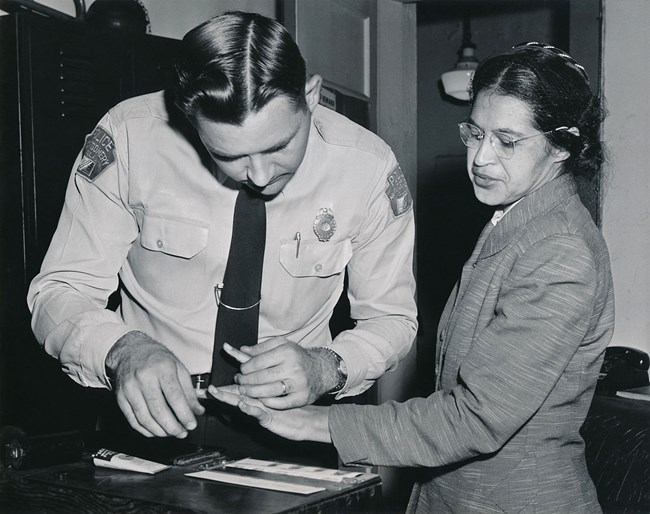 Rosa Parks being fingerprinted by Deputy Sheriff D.H. Lackey after being arrested on February 22, 1956, during the Montgomery bus boycott.
