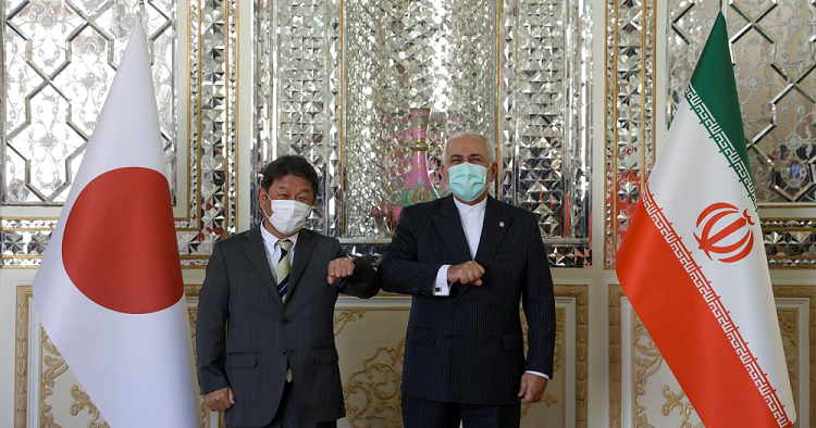 Foreign Minister Mohammad Javad Zarif and Japanese Foreign Minister Toshimitsu Motegi bump elbows during a meeting in Tehran [Majid Asgaripour/WANA via Reuters]