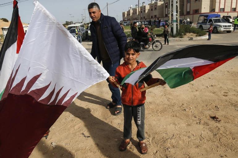 Child waving Qatari and Palistinian Flag