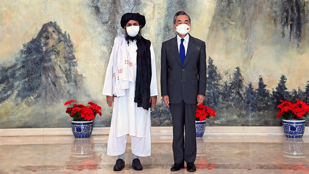 Taliban co-founder Mullah Abdul Ghani Baradar (L) and Chinese Foreign Minister Wang Yi (R) pose for a photo during a meeting in Tianjin, China, July 28, 2021, as ties between them warm ahead of the US pullout from Afghanistan..