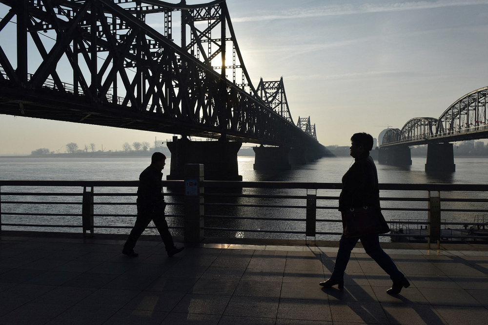 People walk below the Friendship Bridge, which spans the Yalu River between China and North Korea, in the Chinese city of Dandong, Feb. 22, 2019.
