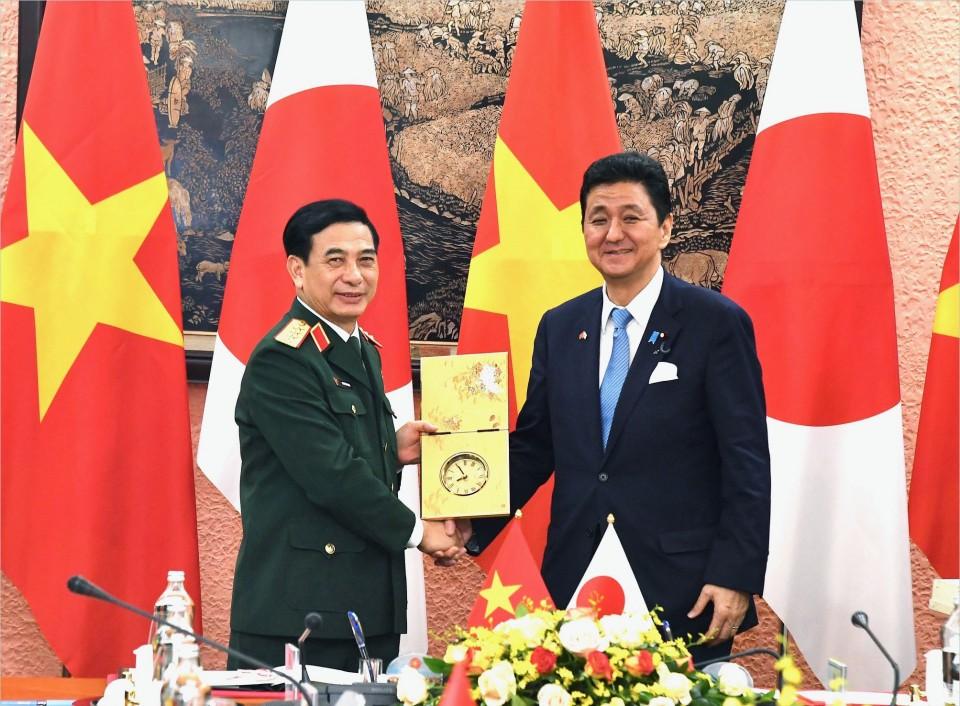 Japan's Defense Minister Nobuo Kishi and his Vietnamese counterpart Phan Van Giang shake hands in Hanoi, Vietnam,