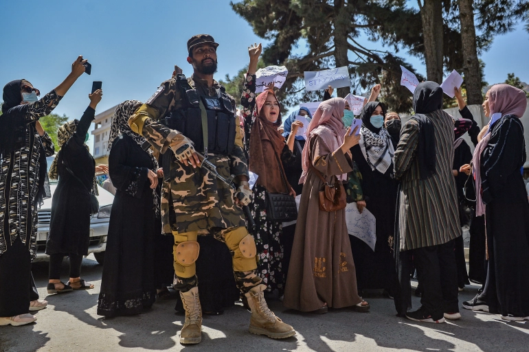 A Taliban fighter stands guard as Afghan women shout slogans during a protest in Kabul [Hoshang Hashimi/AFP]